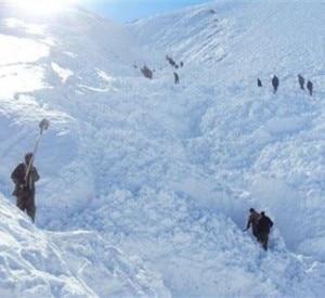 La popolazione afghana scava sotto una valanga per cercare superstiti (Photo Reuters)