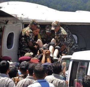 I militari nepalesi caricano uno dei sopravvissuti sull'aereo che lo porterà in ospedale ( Krishnamani Baral / AP Photo)