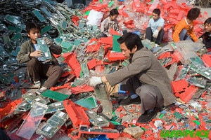 Chinese workers tak apart electronic trash on the street in Guiyu, China.