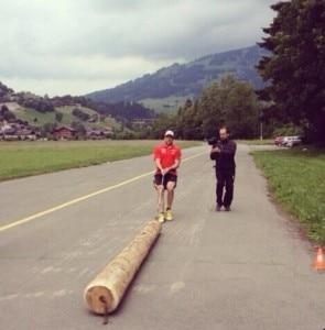 Un atleta della squadra di sci svizzera mentre trascina un tronco d'albero durante l'allenamento (Photo courtesy of FIS twitter account)