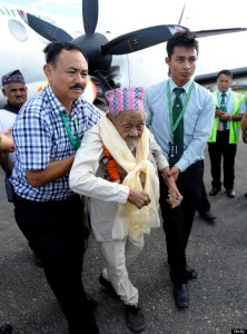 In this file photo, Bote Rai (C), 106, receives assistance on the tarmac after flying for the first time during his arrival at the Kathmandu airport on August 20, 2013. File Photo: AFP