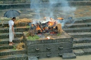 In this file photo, a priest watches a funeral pyre at a cremation in Nepal.