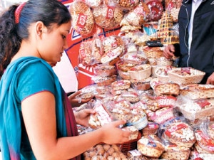A shopper buying dry fruits for Tihar at a shop in Ason, the central market place in Kathmandu. Photo: NMF