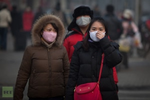 In this file photo by AFP, pedestrians wearing masks wait to cross a road during severe pollution in Beijing on January 12, 2013.