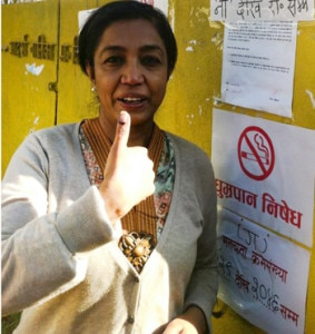 A woman points out a mark at her finger as a proof for casting a vote. Photo: NMF
