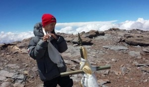 This photo released by Lhawang Dhondup shows 9-year-old Tyler Armstrong standing by a cross on the summit of the 22,841-foot Aconcagua Mountain in Argentina on Tuesday. Source: AP