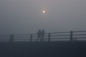 Two men walk along the bride on a foggy morning in Kathmandu as the Sun shines low in the backdrop. Photo: File photo/NMF