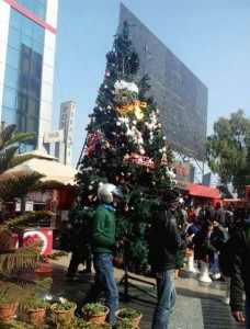 People walk by a X-Mas Tree set at the premises of a shopping mall in Kathmandu. Photo:NMF