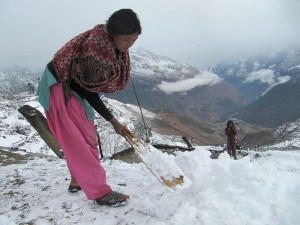 A woman clears snow from the rooftop in Mathitum village in mountainous Mugu district on Saturday. Photo: ekantipur.com