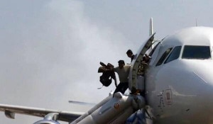 Passengers jump through emergency slide exits after the plane caught fire. Photo source: ANI/Facebook Post