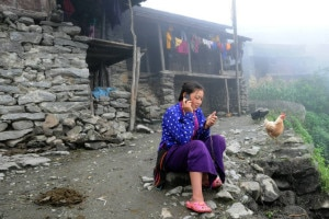 a woman in Haku village in Rasuwa district talks on her mobile phone. Once affordable only for the wealthy, over the past few years mobile phones have become cheaper and more available. Image credit to Chandra Shekhar Karki.