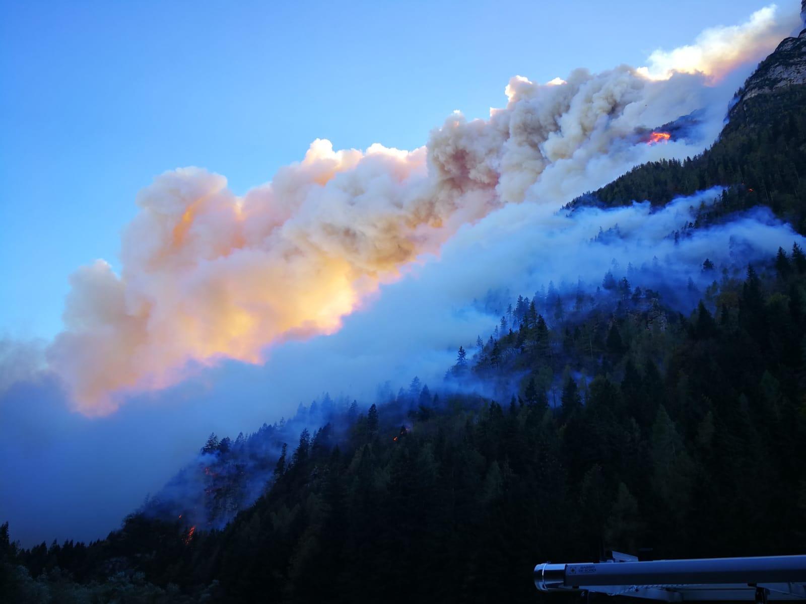 Photo of Fiamme sull'Agordino, cala il vento. Tratti in salvo i due escursionisti bloccati dall'incendio