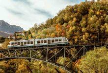 Photo of Tra boschi alpini tinti d'autunno a bordo del Treno del Foliage